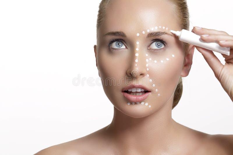 Jeune belle femme appliquant la crème sur sa peau photos libres de droits