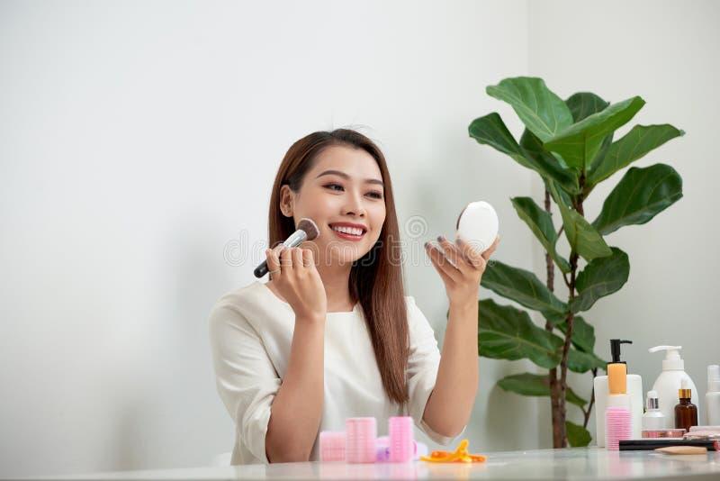 Jeune belle femme appliquant son maquillage avec une grande brosse, regardant dans un miroir image libre de droits