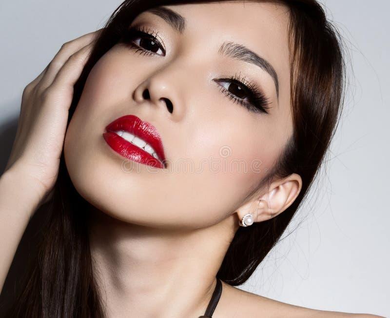 Jeune belle femme asiatique avec la peau impeccable et les cheveux de maquillage et bruns parfaits image libre de droits