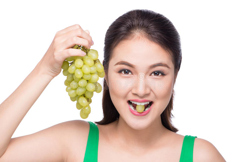 Jeune belle femme asiatique mangeant les raisins frais d'isolement sur le petit morceau image libre de droits