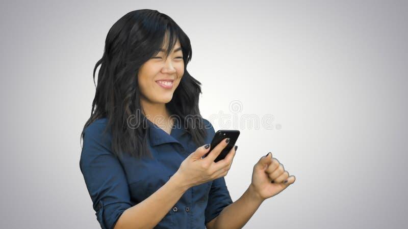 Jeune belle femme asiatique positive employant le téléphone portable, la danse et le sourire sur le fond blanc photo stock