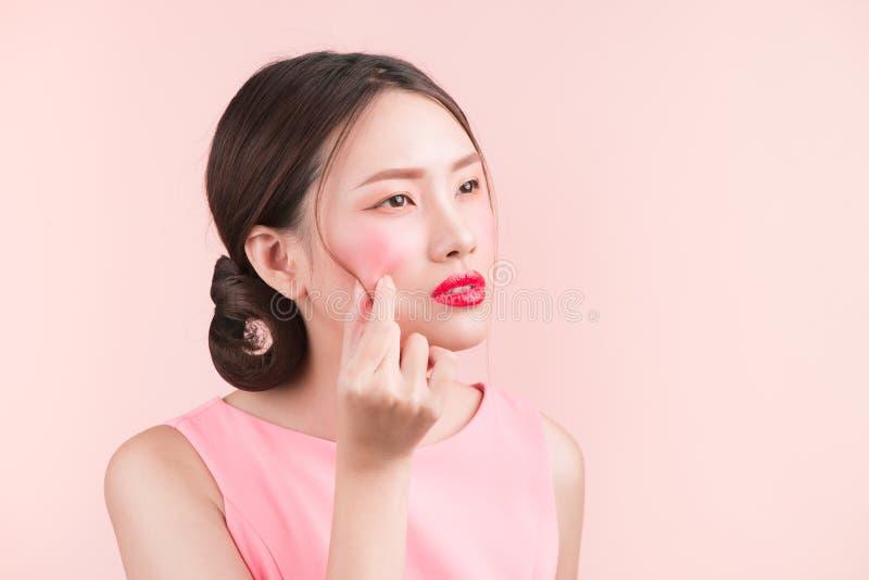 Jeune belle femme asiatique serrant et enlevant son bouton image stock