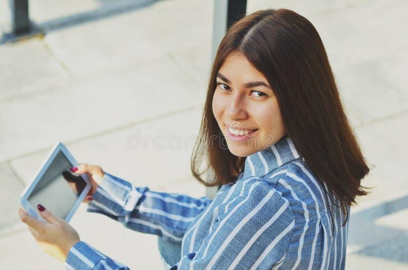 Jeune belle femme asiatique souriant à la caméra et tenant un comprimé dans des ses mains images stock