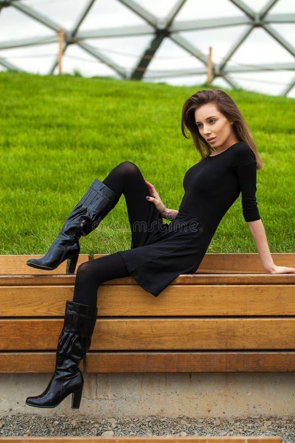 Belle fille brune, assis sur un banc dans le parc