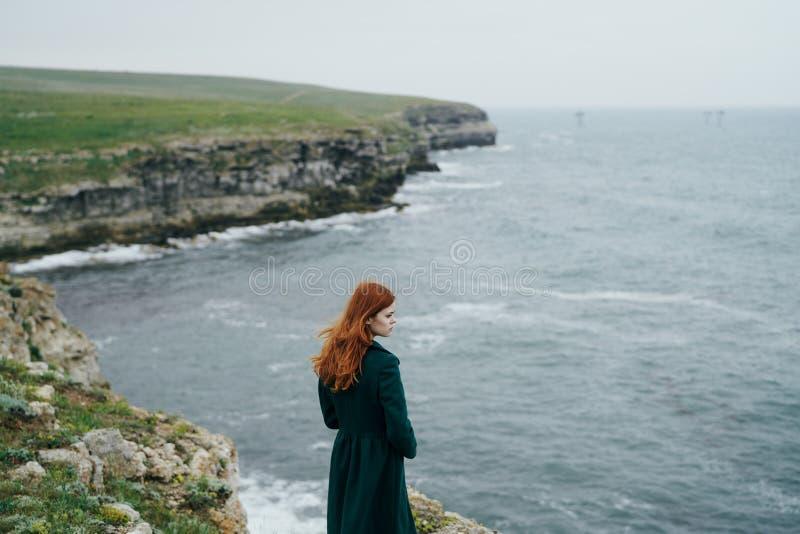 Jeune belle femme au bord d'une falaise près de la mer image libre de droits