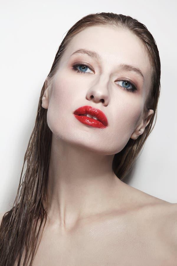 Jeune belle femme aux cheveux mouillés et aux lèvres rouges photo stock