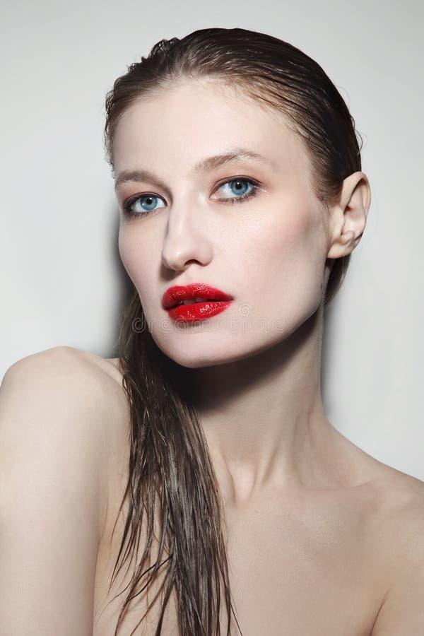 Jeune belle femme aux cheveux mouillés et aux lèvres rouges photos stock