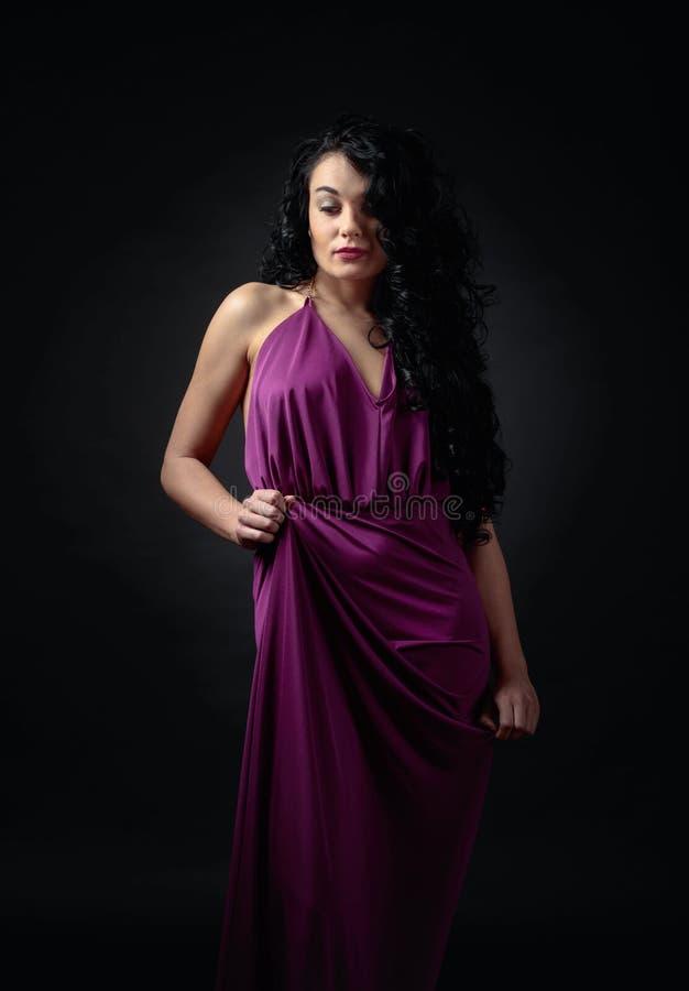 Jeune belle femme avec de longs cheveux bouclés dans la robe de soirée image stock