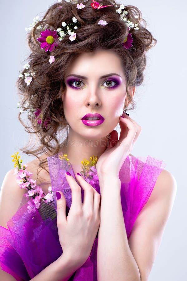 Jeune belle femme avec des fleurs dans ses cheveux et maquillage lumineux images libres de droits