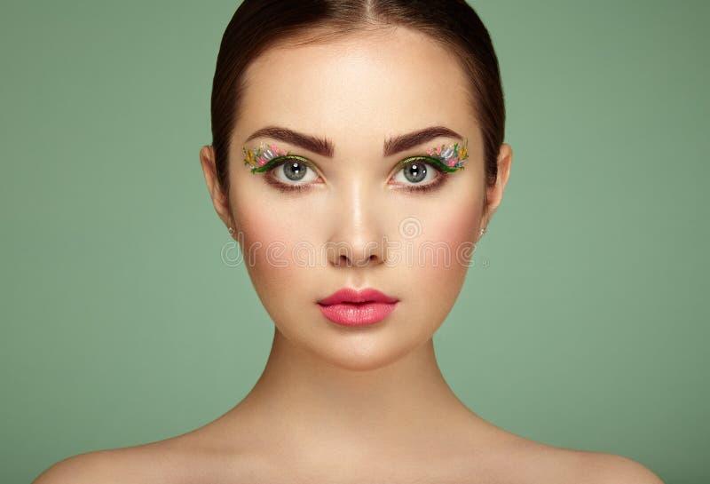 Jeune belle femme avec des yeux de maquillage de fleur photo stock
