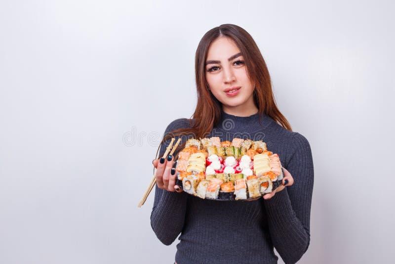 Jeune belle femme avec l'ensemble de baguettes et de sushi, studio oust photographie stock