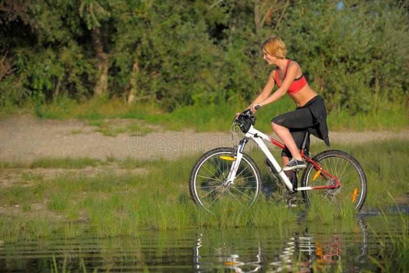 Jeune belle femme avec la bicyclette passant par l'eau par la rivière images libres de droits