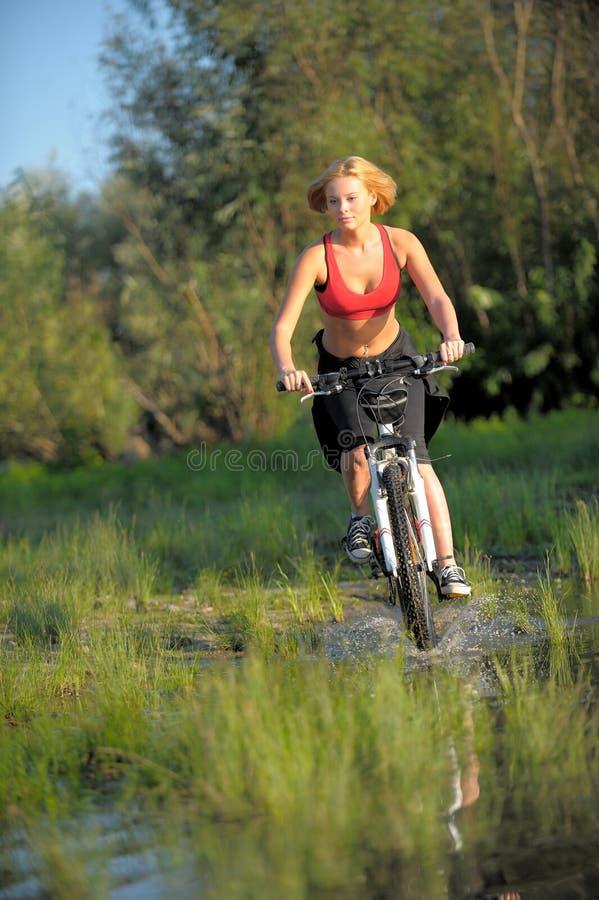 Jeune belle femme avec la bicyclette passant par l'eau par la rivière photos stock