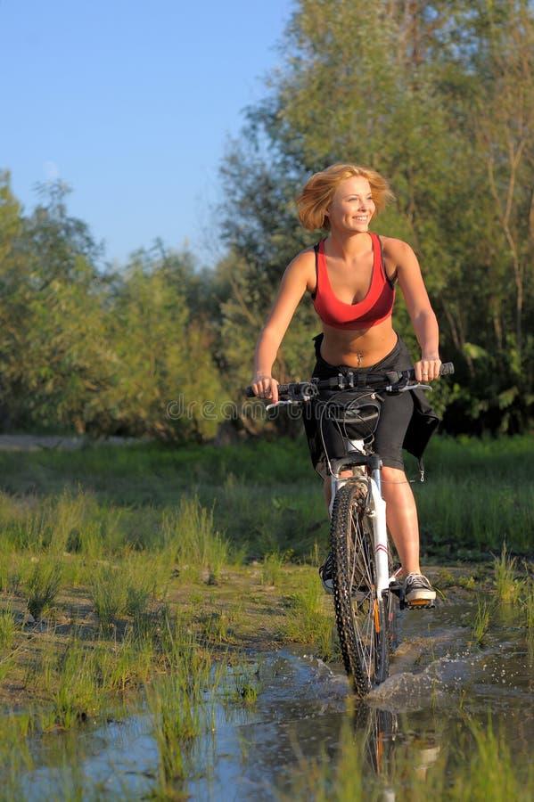 Jeune belle femme avec la bicyclette passant par l'eau par la rivière photo libre de droits