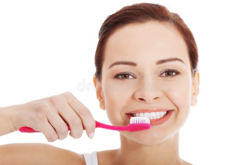 Jeune belle femme avec la brosse à dents et la pâte. images stock