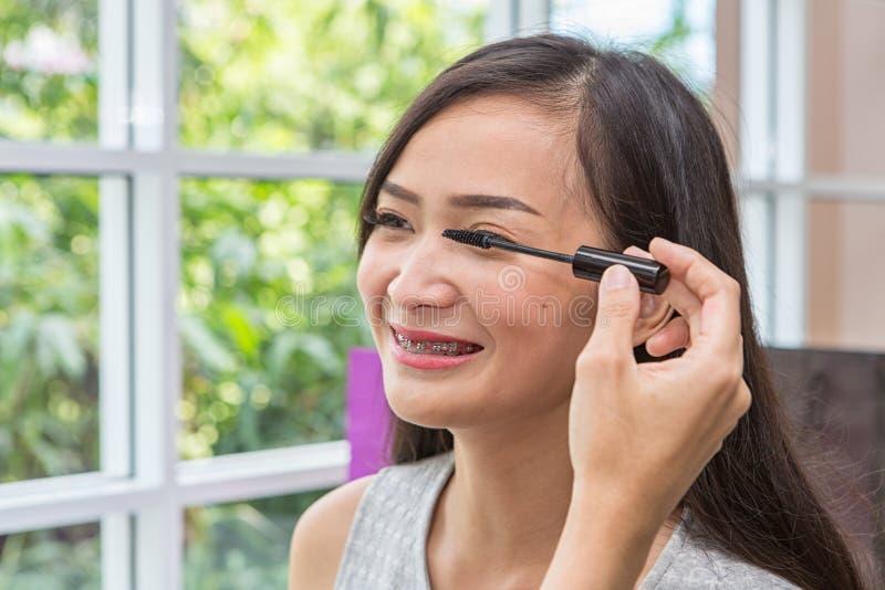 Jeune belle femme avec la brosse de maquillage Deux amis composant dans le café Fille asiatique Les amis sont brosse de mascara photographie stock libre de droits
