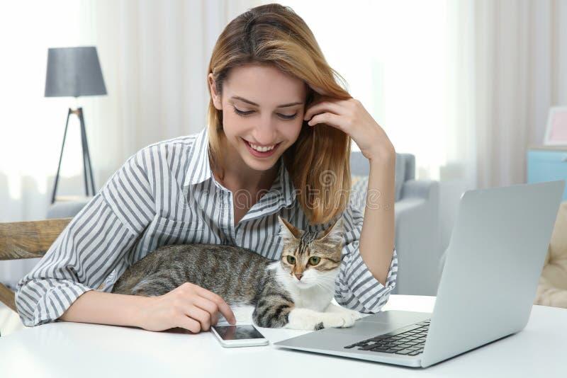 Jeune belle femme avec le chat utilisant l'ordinateur portable photographie stock