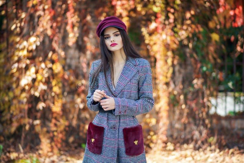 Jeune belle femme avec le manteau et le chapeau de port d'hiver de cheveux très longs à l'arrière-plan de feuilles d'automne photos stock