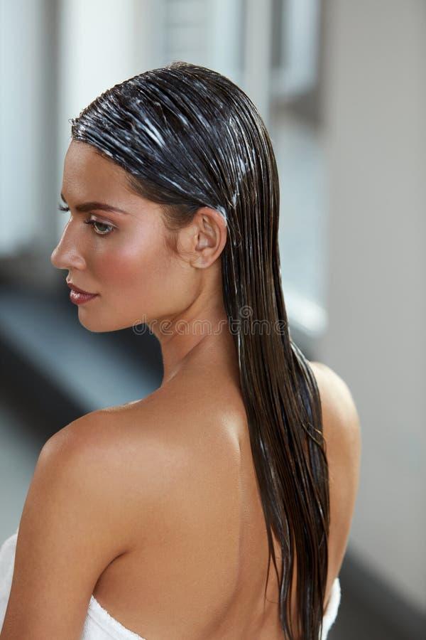 Jeune belle femme avec le masque naturel appliqué de cheveux Soins capillaires photos libres de droits