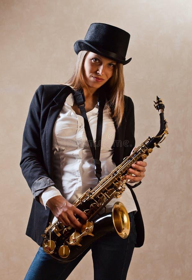 Jeune belle femme avec le saxophone images libres de droits