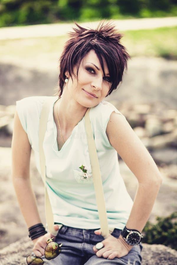Jeune belle femme avec les cheveux courts se reposant sur une pierre images libres de droits