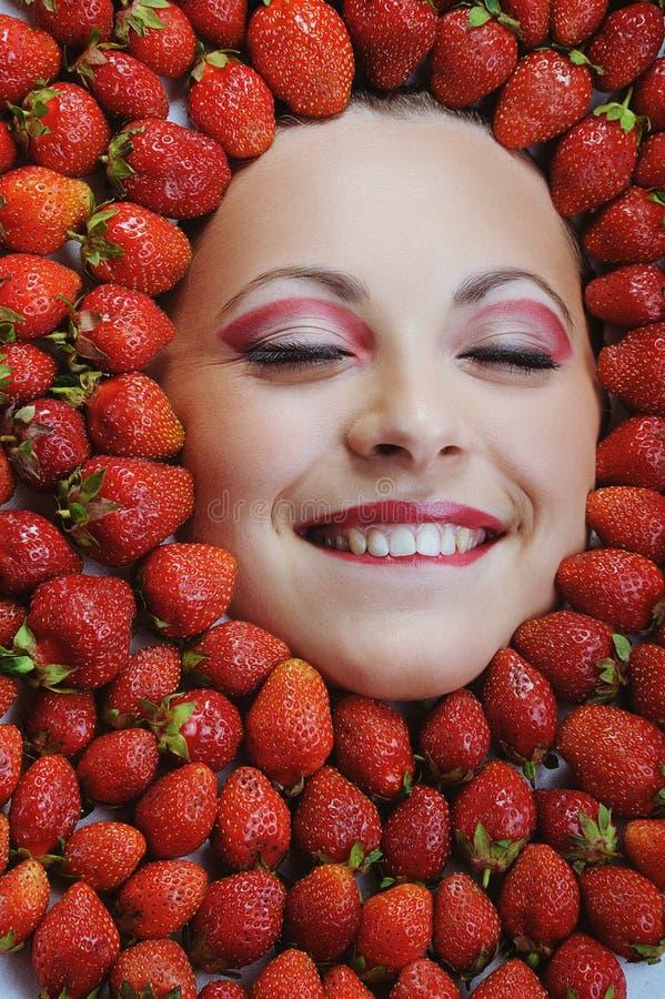 Jeune belle femme avec les dents blanches fermant ses yeux sur le fond de fraises photos stock