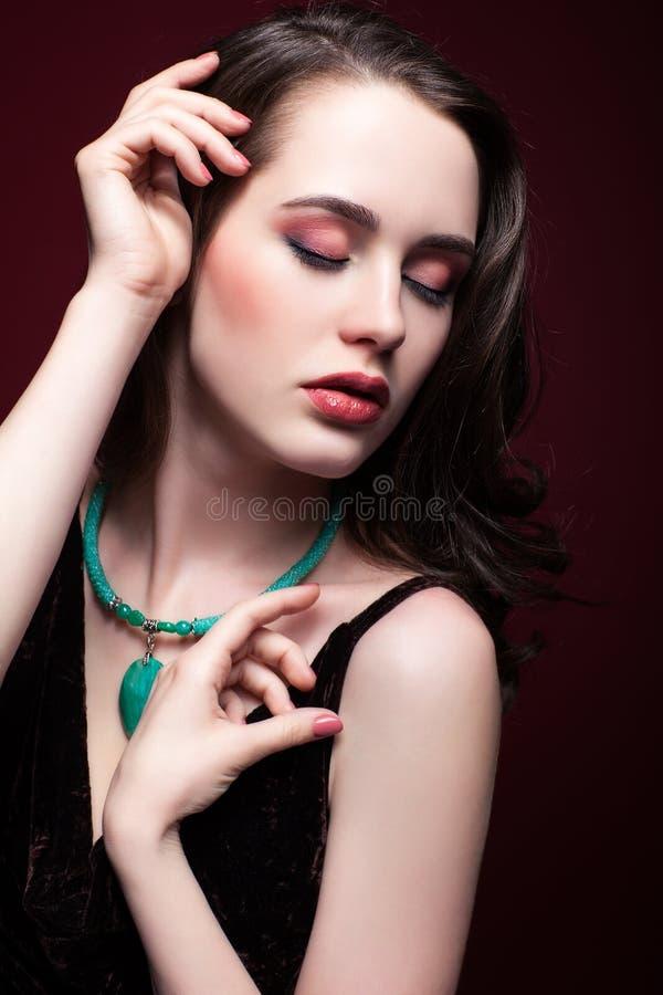Jeune belle femme avec les yeux fermés sur le fond rouge de marsala photo stock
