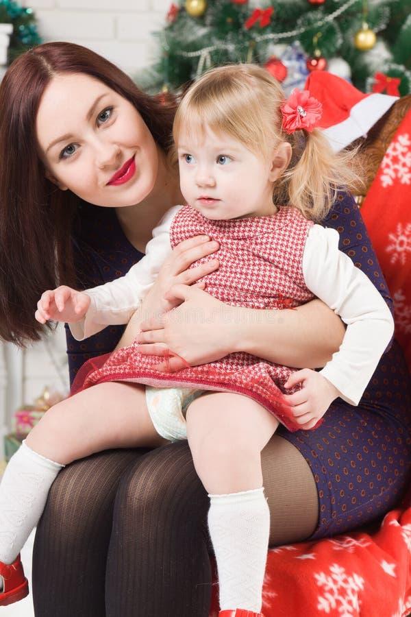 Jeune belle femme avec sa fille près de l'arbre de Noël image stock