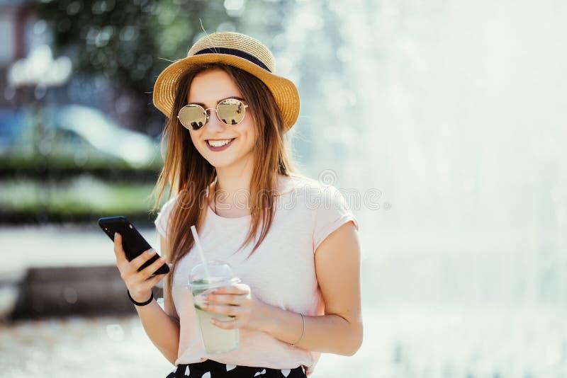 Jeune belle femme avec une boisson froide se reposant dans la rue dactylographiant au téléphone image stock