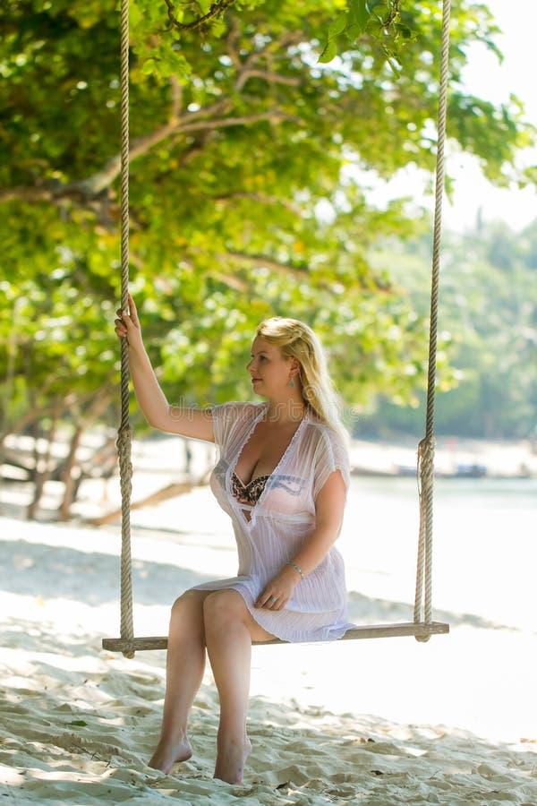 Jeune belle femme blonde à la plage dans le bikini balançant sur une oscillation photo libre de droits