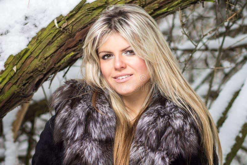 Jeune belle femme blonde posant à la forêt d'hiver photographie stock