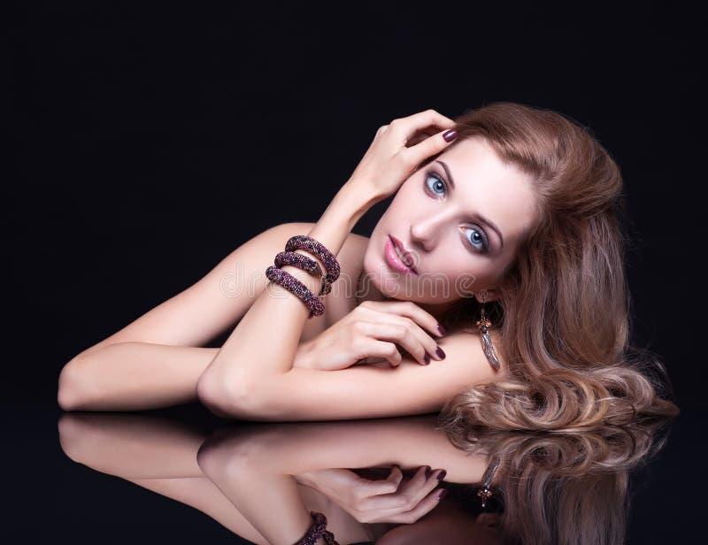 Jeune belle femme blonde s'asseyant à la table de miroir sur le Ba noir image stock