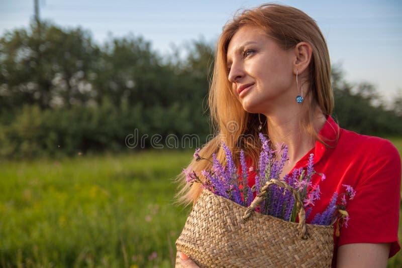 Jeune belle femme blonde smilling avec des fleurs en nature pendant l'été images stock