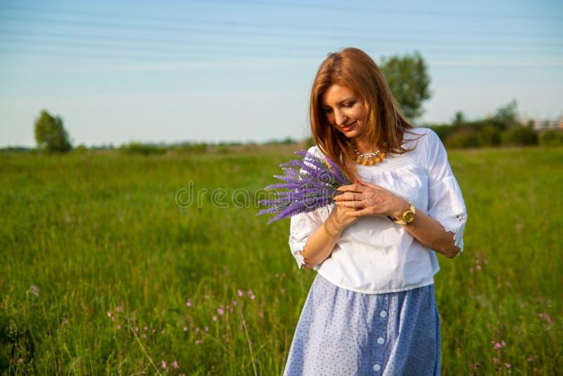 Jeune belle femme blonde smilling avec des fleurs en nature pendant l'été image libre de droits