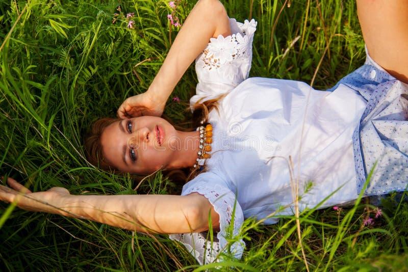 Jeune belle femme blonde smilling avec des fleurs en nature pendant l'été photos libres de droits