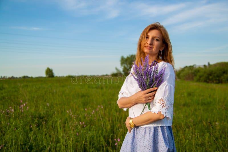 Jeune belle femme blonde smilling avec des fleurs en nature pendant l'été images libres de droits