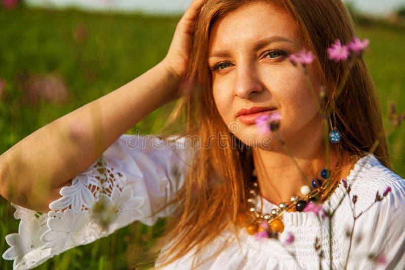 Jeune belle femme blonde smilling avec des fleurs en nature pendant l'été photographie stock