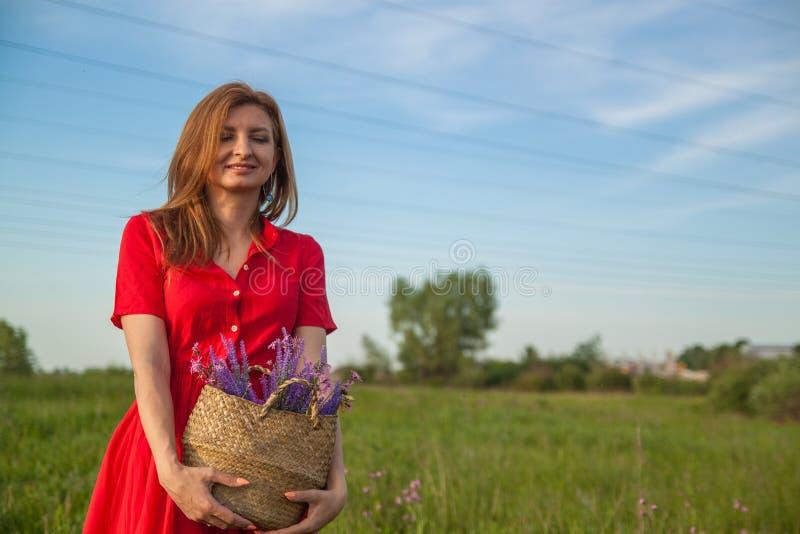 Jeune belle femme blonde smilling avec des fleurs en nature pendant l'été image stock