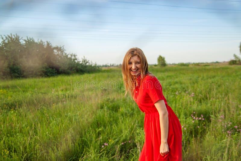 Jeune belle femme blonde smilling avec des fleurs en nature pendant l'été photo libre de droits