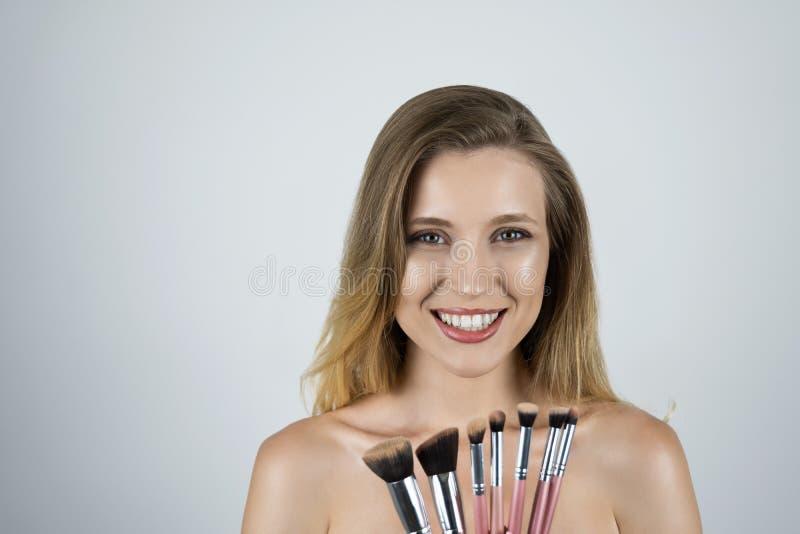 Jeune belle femme blonde tenant le fond blanc d'isolement par brosses roses images stock