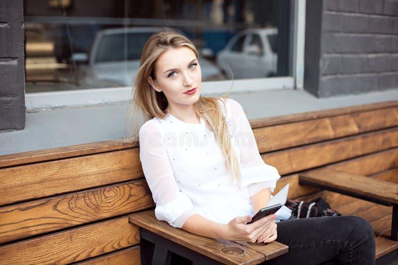 Jeune belle femme blonde tenant un téléphone portable tout en se reposant avec un livre portatif de réseau dans un intérieur de c photographie stock