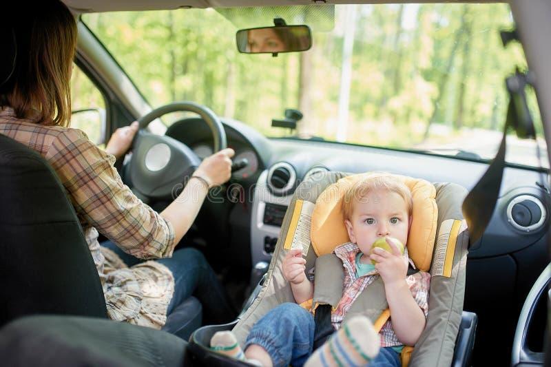 Jeune belle femme conduisant une voiture Sur un siège avant a monté le siège de sécurité pour enfants avec un garçon assez de 1 a image libre de droits