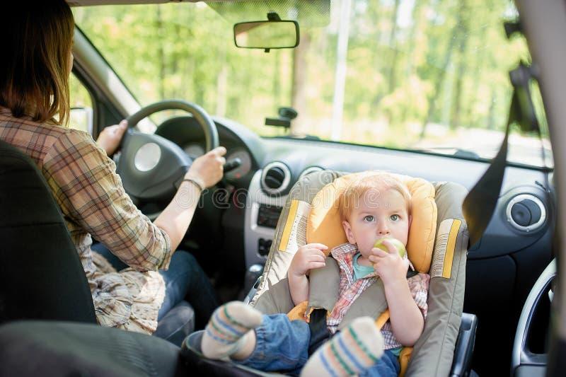 Jeune belle femme conduisant une voiture Sur un si?ge avant a mont? le si?ge de s?curit? pour enfants avec un gar?on assez de 1 a photo stock