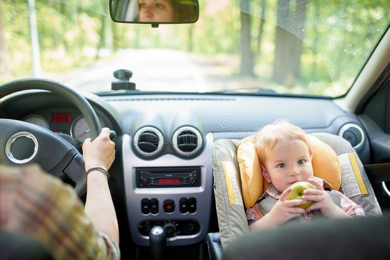 Jeune belle femme conduisant une voiture Sur un si?ge avant a mont? le si?ge de s?curit? pour enfants avec un gar?on assez de 1 a image libre de droits