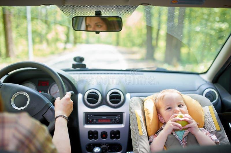 Jeune belle femme conduisant une voiture Sur un si?ge avant a mont? le si?ge de s?curit? pour enfants avec un gar?on assez de 1 a photo libre de droits