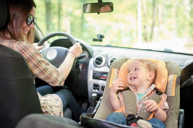 Jeune belle femme conduisant une voiture Sur un si?ge avant a mont? le si?ge de s?curit? pour enfants avec un gar?on assez de 1 a images stock
