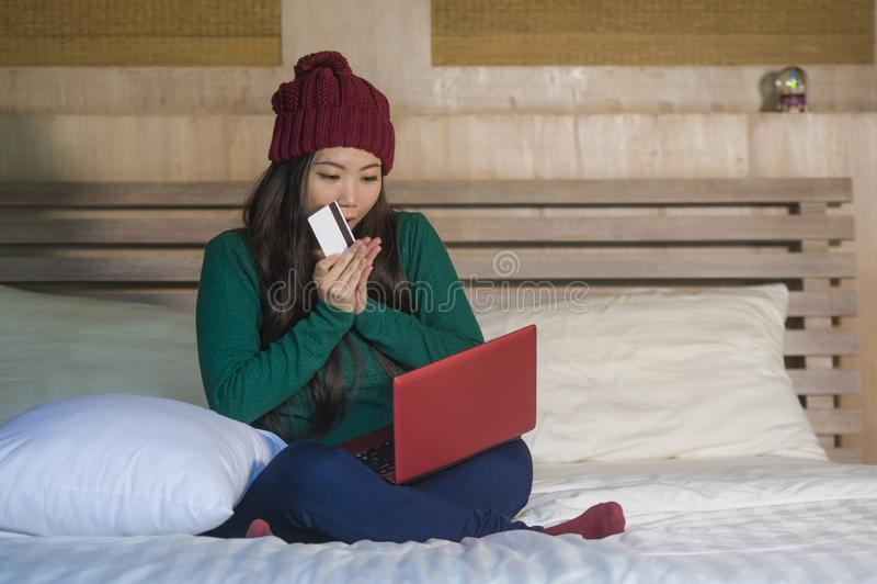 Jeune belle femme coréenne asiatique heureuse dans le chapeau d'hiver détendu sur le lit tenant la carte de crédit utilisant l'or photos stock