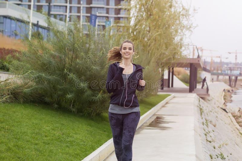 Jeune belle femme courant dans le milieu urbain image libre de droits