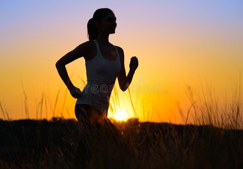 Jeune belle femme courant sur la traînée de montagne pendant le matin photographie stock libre de droits