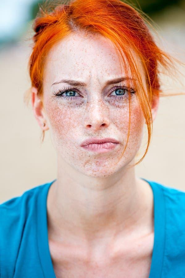 Jeune belle femme couverte de taches de rousseur rousse préoccupée photos stock